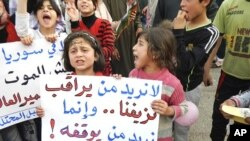 """Demonstrators take part in a protest against Syria's President Bashar Al-Assad in Kafranbel, near Idlib May 1, 2012. Poster reads: """"No need to observe our bleeding..we want who can stop it""""."""