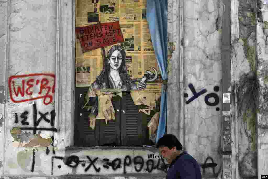 """A man walks past political graffiti reading """"Bid! a few items left on sale"""" by artist Bleeps, in central Athens, one day after Greece and its creditors closed a troubled period on fiscal reforms."""