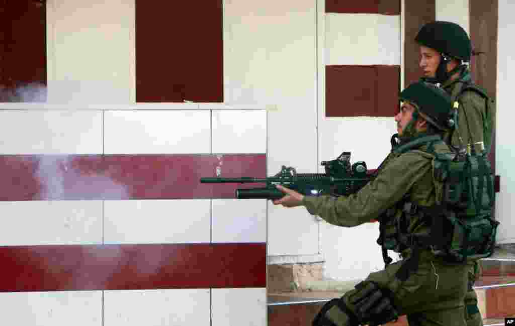 Israeli army soldiers fire tear gas during clashes with Palestinians in an operation in the West Bank city of Jenin, July 2, 2014.