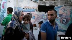 一名痛哭的婦女抱著她的兒子在加沙北部一所聯合國開辦的收留因以色列炮擊而無家可歸的巴勒斯坦人的學校7月30日遭以色列炮彈襲擊後的情形。