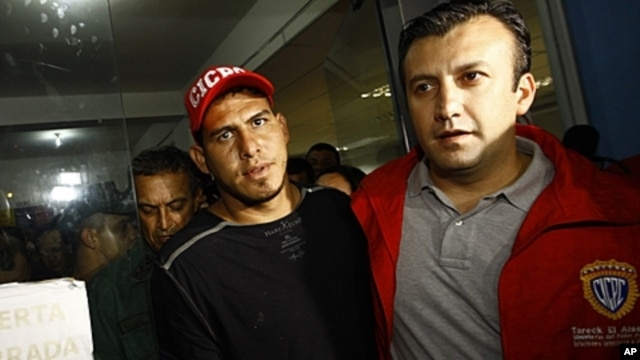 Washington Nationals' catcher Wilson Ramos, left, is seen at the Criminal Police (CICPC) headquarters accompanied by Venezuela's Justice Minister Tareck El Aissami  in Valencia, Venezuela, November 12, 2011.