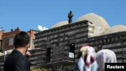Diyarbəkirin Sur məhəlləsində polis zabiti bina üzərində dayanıb keşik çəkir.