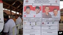 Poster bergambar kedua kandidat presiden dan wakil presiden di sebuah tempat pemungutan suara di Bali (9/7). (AP/Firdia Lisnawati)