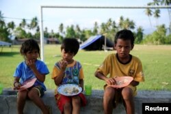Children eat outside their tent for safety reasons after the earthquake in Biromaru village in Sigi, in Indonesia's Sulawesi island, Oct. 3, 2018.