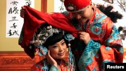 Một cặp đôi đính hôn trong trang phục cưới truyền thống của Trung Quốc chụp ảnh cưới ở một studio ở trung tâm Bắc Kinh. Đàn ông ở nông thôn Trung Quốc ngày càng có ít cơ hội lấy được vợ vì 'giá cô dâu' tăng cao.