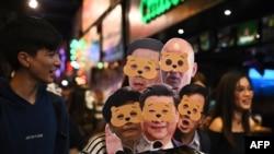 Mwanamke amevaa nyuso za bandia kadhaa za Kiongozi wa Hong Kong Carrie Lam (kushoto chini) na Rais wa China Xi Jinping (katikati chini) wakiandamana wakati wa sikukuu ya Halloween, Hong Kong, Octoba 31, 2019.