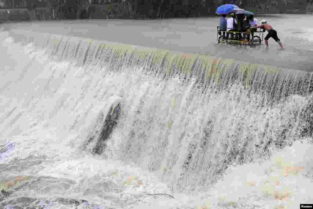 Residents cross a swelling dam due to rising waters brought about by Typhoon Koppu, in Las Pinas city, metro Manila. Typhoon Koppu swept across the northern Philippines, killing at least nine people as trees, power lines and walls were toppled and flood waters spread far from riverbeds, but tens of thousands of people were evacuated in time.