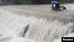 Cư dân vượt qua một con đập bị nước lũ dâng cao vì bão Koppu tại thành phố Las Pinas ở Manila, ngày 19/10/2015.