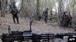 Karen National Union (KNU) soldiers stand guard with their assault weapons at Oo Kray Kee village in Karen State near Thai-Myanmar border on January 30, 2012. The Karen National Union (KNU) is waging the world's longest-running insurgency, launched 63 yea