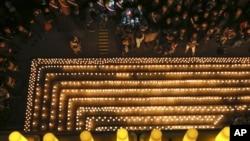 在法国中部的里昂,人们聚集在烛光周围,哀悼巴黎《查理周刊》杂志社枪击惨案死难者。(2014年1月7日)