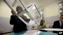 Petugas pemilu Aljazair melakukan perhitungan kartu suara di salah satu TPS di ibukota Algiers (10/5).