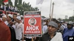 """Seorang pendemo memegang poster dalam demonstrasi di Monas, untuk memprotes Gubernur Jakarta Basuki """"Ahok"""" Tjahja Purnama yang pada saat itu menjalani sidang penodaan agama, 2 Desember 2017."""