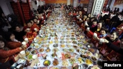 "In this 2014 photo, residents of Wuhan, a city in China's Hubei province, share a meal during the Chinese Lunar New Year. The event is called ""Ten Thousand Families Dinner."" (Photo Reuters)"
