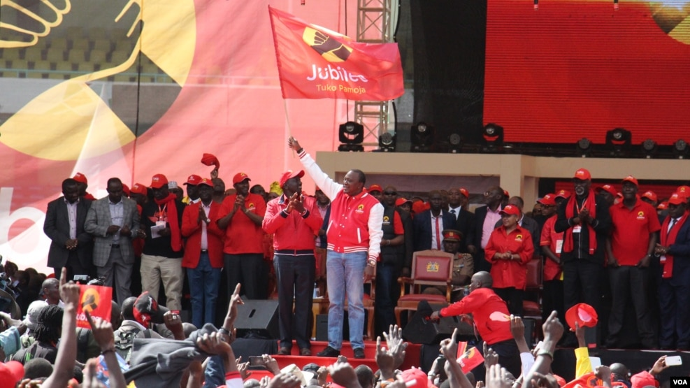 President Uhuru Kenyatta waves the Jubilee Party flag to the crowd as he launches the party he will use to run for office in 2017 polls, Sept. 10, 2016. (M. Yusuf/VOA)
