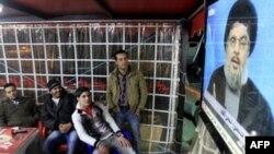 Người dân ở Li Băng theo dõi bài phát biểu của lãnh đạo Hezbollah Hassan Nasrallah trên truyền hình tại một quán cà phê ở thành phố cảng miền nam Sidon, ngày 16/1/2011. Tuần trước, phe Hezbollah và đồng minh của họ đã rời bỏ chính phủ do phương Tây hậu th