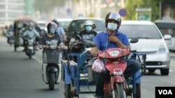 Motorcycle riders wear face masks to curb the spread of COVID-19 in Phnom Penh, Cambodia. (Hean Socheata/VOA Khmer)