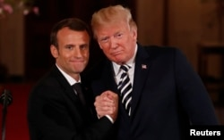 French President Emmanuel Macron clasps hands with U.S. President Donald Trump at the conclusion of their joint news conference in the East Room of the White House in Washington, April 24, 2018.