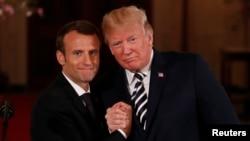 លោកប្រធានាធិបតីបារាំង Emmanuel Macron ចាប់ដៃជាមួយនឹងលោកប្រធានាធិបតី ដូណាល់ ត្រាំ នៅពេលបញ្ចប់សន្និសីទកាសែតរួមមួយនៅសេតវិមាន ក្នុងរដ្ឋធានីវ៉ាស៊ីនតោន កាលពីថ្ងៃទី២៤ ខែមេសា ឆ្នាំ២០១៨។