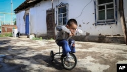 Alif Baqytali plays on a tricycle at his home in Shonzhy, Kazakhstan on June 13, 2020. Baqytali's mother, Gulnar Omirzakh, says she was forced to get a contraceptive device, and that authorities threatened to detain her if she didn't pay a large fine for giving birth to him. (AP)