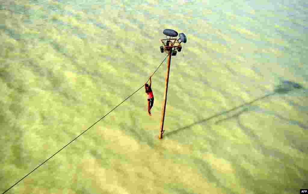 Indijac, tinejdžer, visi na kablu prije nego će pasti vodu izlivenog, nabujalog, Ganga nedaleko od Alahabada.