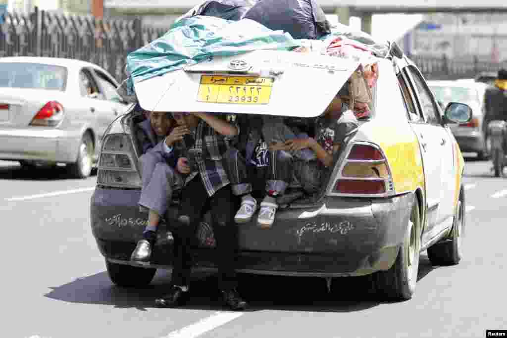 Boys sit in the boot of a car in Sana'a, Yemen.