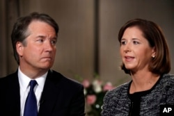 Brett Kavanaugh, left, looks at his wife Ashley Estes Kavanaugh as they answer questions during a FOX News interview, Sept. 24, 2018, in Washington, about allegations of sexual misconduct against the Supreme Court nominee.