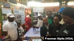 Virginie Baïkoua ministre centrafricaine des affaires sociales, en gros plan à droite, devant une exposition des humanitaires, à Bangui, 19 août 2017. (VOA/Freeman Sipila)