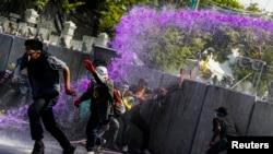 Para demonstran anti-pemerintah melarikan diri seiring penggunaan meriam air oleh polisi anti-huru hara dalam bentrokan dekat markas polisi Bangkok (2/12).