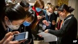 带着口罩的记者们阅读中国政府有关新冠病毒的声明(2020年1月26日资料照片)