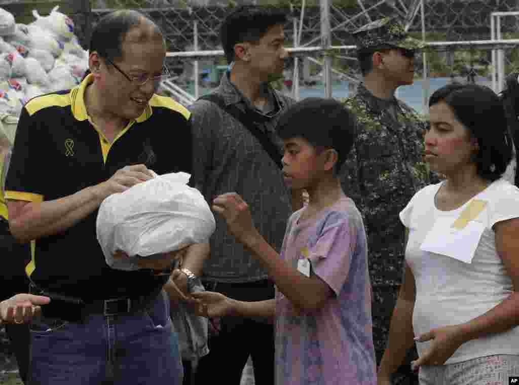 Presiden Filipina Benigno Aquino (kiri) membantu mendistribusikan makanan bantuan untuk penyintas Topan Bopha di New Bataan, Compostela Valley (7/12). (AP/Bullit Marquez)