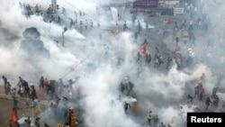 Người biểu tình hoảng loạn bỏ chạy khi cảnh sát chống bạo động quay lại Quảng trường Taksim ở Istanbul chiều 11/6 và xịt hơi cay. (Reuters)
