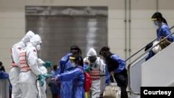 台湾防化兵在对从武汉飞抵桃园机场包机的台湾人进行防疫消毒作业。(台湾国防部军闻社提供)