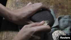 Pedagang emas memakai batu untuk menilai tingkat dan harga bongkahan emas di Diwalwal, Filipina Selatan.(Foto: Reuters)