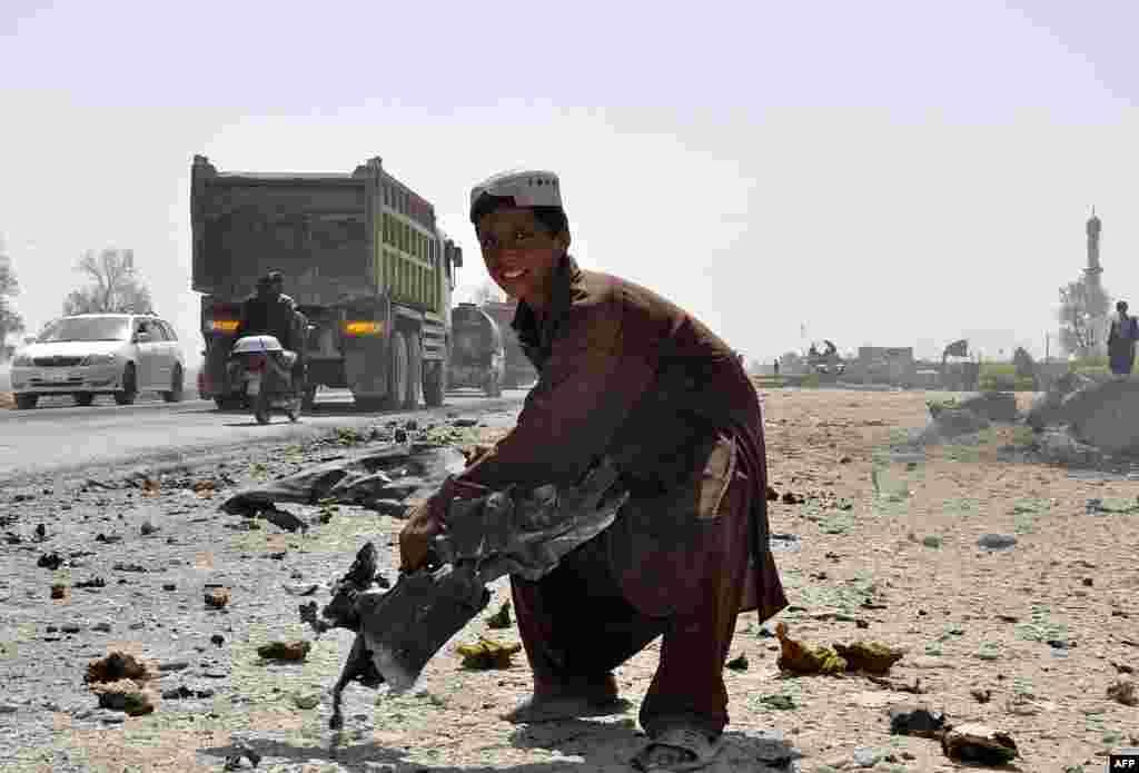 Một cậu bé người Afghanistan nâng một mảnh kim loại cong vẹo văng ra từ một chiếc xe tại một nơi nổ bom ở Kandahar, Afghanistan.