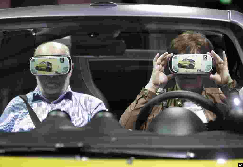 ស្រី្តម្នាក់យកដៃស្ទាបវ៉ែនតានិម្មិតរូបភាព 3D ខណៈដែលអ្នកស្រីនិងបុរសម្នាក់ទៀតអង្គុយក្នុងឡានមួយមុននឹងកិច្ចប្រជុំភាគហ៊ុនិកនៃក្រុមហ៊ុន Daimler AG ទីក្រុង ប៊ែកឡាំង ប្រទេសអាល្លឺម៉ង់។