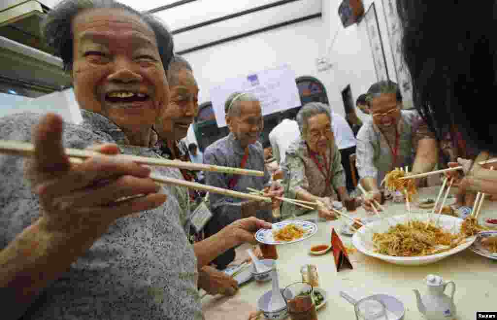 在農歷新年來臨之前,老年居民們在新加坡中國城一座餐館裡撈魚生。