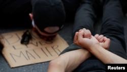 Para pengunjuk rasa berpose seperti sedang diamankan dalam unjuk rasa memprotes kematian George Floyd, di Boston, Massachusetts, 4 Juni 2020. (Foto: Reuters)