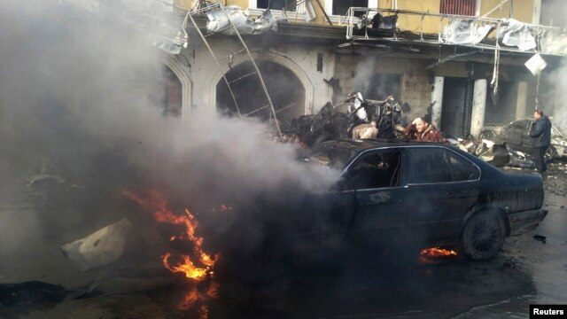 A man reacts near a burning car at the site of an explosion in the Shi'ite town of Hermel, Jan. 16, 2014.