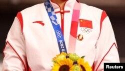 東京奧運會田徑單車女隊金牌得主包善菊佩戴毛澤東徽章接受頒獎。