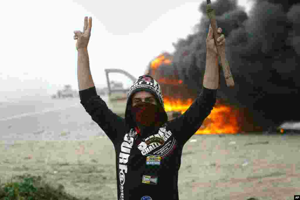 A protester in front of a vehicle destroyed by protesters in Fallujah, Iraq, January 25, 2013.