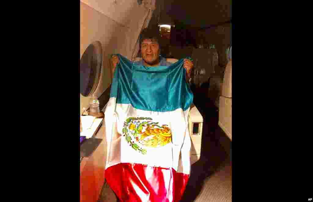 En esta imagen publicada por el ministro mexicano de Exteriores, Marcelo Ebrard, se ve al expresidente de Bolivia Evo Morales sosteniendo una bandera mexicana a bordo de un avión de la Fuerza Aérea mexicana, el lunes 11 de noviembre de 2019.