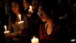 Natalynn Rivis, a student at University of Nevada Las Vegas, right, takes part in a vigil Monday, Oct. 2, 2017, in Las Vegas, Nevada.