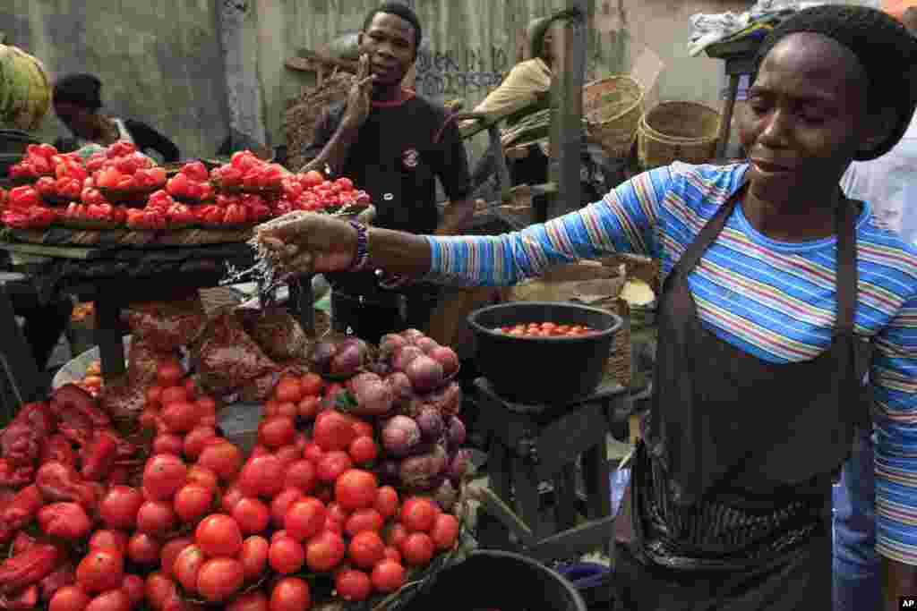 NIGERIA: Strikes by labor unions protesting high gasoline prices caused damage to fresh produce inventories. A woman sells tomatoes at a market in Obalende, Lagos, Nigeria, Saturday, Jan. 14, 2012.
