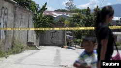 FILE - A woman and a child walk past a crime scene where the body of a dead man was found after he was shot by alleged gang members in the El Castillo neighborhood in Soyapango, on the outskirts of San Salvador, El Salvador, July 20, 2015.