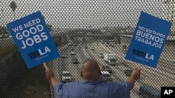 """South Los Angeles resident Christian Del Cid waves banners calling for good jobs, on a bridge in front of oncoming traffic at the Interstate I-110 overpass on a """"structurally deficient"""" bridge to call on U.S. Congress to provide funding for highway improv"""