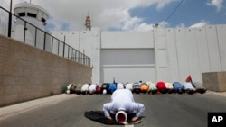 Palestinians perform Friday Prayers in front of a checkpoint along Israel's separation barrier during a demonstration to support prisoners on hunger strike in Israeli jails, West Bank town of Bethlehem, June 6, 2014.