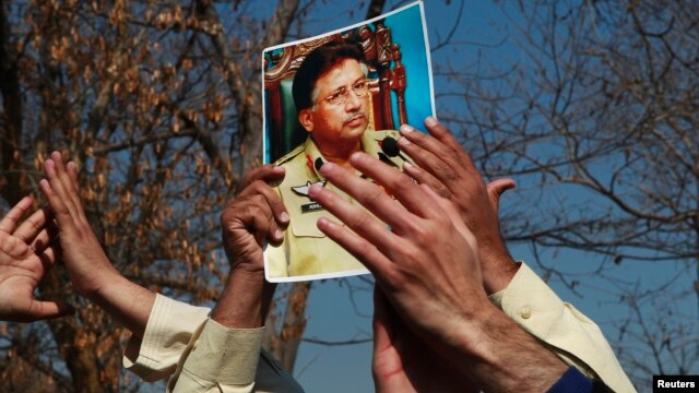 FILE - A supporter holds a picture of former Pakistani President Pervez Musharraf, during a protest with others at the Special Court where Musharraf will attend his trial in Islamabad, Feb. 18, 2014.