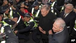 ພະ Cardinal George Pell, ກາງຈາກຂວາ, ຖືກອ້ອມລ້ອມ ໂດຍຕຳຫຼວດ ໃນຂະນະທີ່ເພີ່ນໄປຮອດ ສານຊັ້ນຕົ້ນ ໃນນະຄອນ Melbourne, ອອສເຕຣເລຍ, ວັນທີ 26 ກໍລະກົດ 2017.