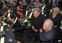 FILE - Cardinal George Pell, center right, is surrounded by police as he arrives at the Melbourne Magistrates Court in Melbourne, Australia, July 26, 2017.