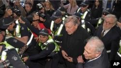 Cardinal George Pell akikujwe n'igiporisi igihe yashika ku nzu y'urukiko i Melbourne, Australiya, itariki 26/07/2017.